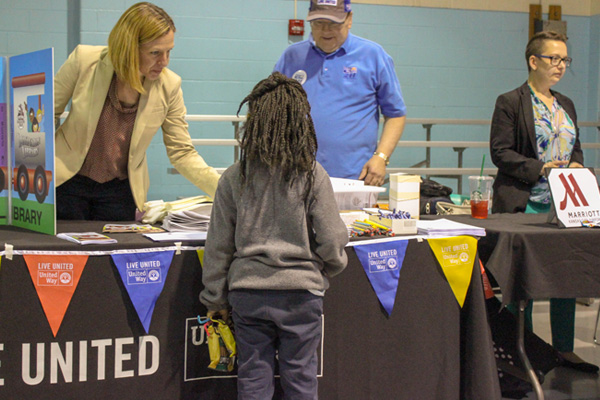 Child receives help at an event table.